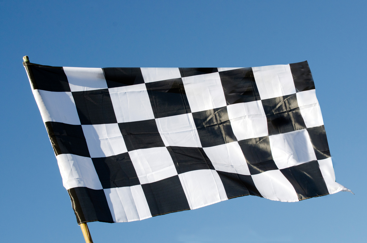 Checkered flag isolated on blue sky background